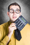 Finance office worker thinking with big calculator. Comical portrait of a stereotypical accounting clerk wearing nerdy glasses holding calculator when working Stock Images