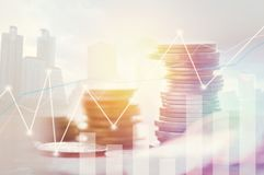 Finance, profit, capital banking and investment concept, Double. Exporsure stacked of coins and night city with graph Royalty Free Stock Photography