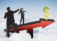 Finance and puppetting concept. Abstract image of businessman placing subordinate on red arrow scales with golden dollar sign on sky background. Finance and Stock Image