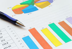 Finance report. Top view of the pen on finance report with colorful charts royalty free stock photo