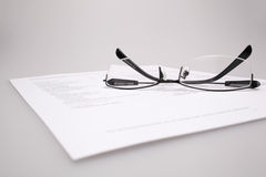 Finance report. Reading finance report with glasses Royalty Free Stock Images