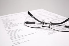 Finance report. Reading finance report with glasses Royalty Free Stock Image