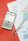 Finance report with a pen and mobile. On red background Royalty Free Stock Photography
