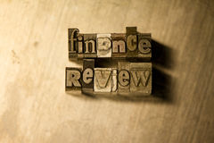 Finance review - Metal letterpress lettering sign. Lead metal  typography text on wooden background Royalty Free Stock Photo