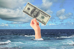 Finance and risk concept. Hand with dollar bill sticking out of ocean. Sky background. Finance and risk concept Stock Photography