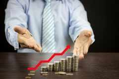Finance and save money concept, Businessman introduce and show h. And at stacked coins with red arrow growing up Stock Photography