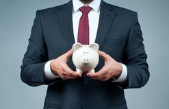 Finance Savings concept. Businessman in suit is holding piggy bank. Royalty Free Stock Photo