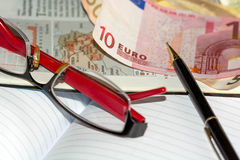 Finance series. Image of selective focus shot of euro banknotes, glasses and black pen on financial pages of broadsheet newspaper Stock Images