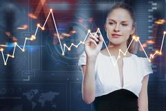 Finance and stock concept. Portrait of attractive smiling young european businesswoman drawing forex chart on blurry background. Finance and stock concept royalty free stock image
