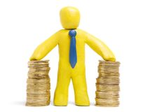 Finance success. Plasticine businessman stands with two heaps of gold coins royalty free stock images