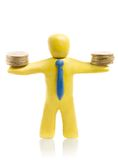Finance success. Plasticine businessman holds two heaps of gold coins royalty free stock image