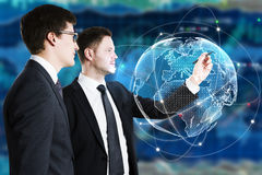 Finance and teamwork concept. Businessmen drawing abstract digital globe on forex background. Finance and teamwork concept. 3D Rendering Royalty Free Stock Images