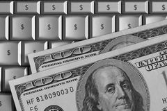 Finance and Technology. Hundred dollar bills on top of a computer. Keyboard characters replaced with dollar signs Royalty Free Stock Images