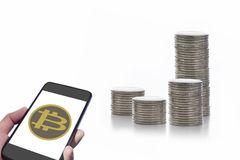 Smartphone with bitcoin exchange and stack of coins on white background Stock Photos