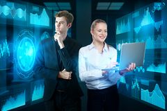 Finance and touchscreen concept. Attractive businesspeople using laptop in blurry interior with abstract business screens. Finance and touchscreen concept. 3D Royalty Free Stock Image