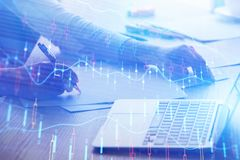 Finance and trade concept. Side view of female hands signing contract at desk with laptop and abstract forex chart. Finance and trade concept. Double exposure royalty free stock image