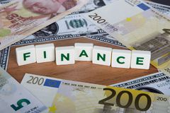 Finance Word with Letters Among Banknotes Stock Images