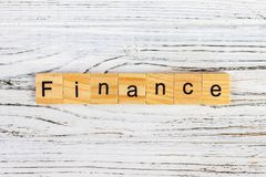 FINANCE word written on wood block on the table Royalty Free Stock Photo