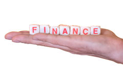 Finance written with wooden dice on a hand, isolated on white background Stock Images