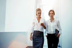 Financeiro bonito da mulher que levanta com tabuleta digital quando sua mensagem de texto da leitura do colega no telefone celula Fotografia de Stock Royalty Free