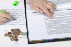 Financeiro na mesa que faz remissão recíproca livros- de algumas vendas Fotos de Stock Royalty Free