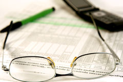 Finances. Glasses, pen and mobile laying on the document Stock Photography