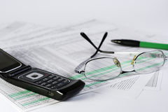 Finances. Glasses, pen and mobile laying on the document Royalty Free Stock Images