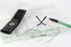 Finances. Glasses, pen and mobile laying on the document Royalty Free Stock Photo