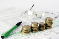 Finances. Pen, glasses and coins laying on document Stock Image
