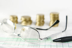 Finances. Pen, glasses and coins laying on document Stock Photos