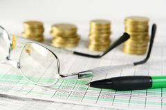 Finances. Pen, glasses and coins laying on document Royalty Free Stock Photos