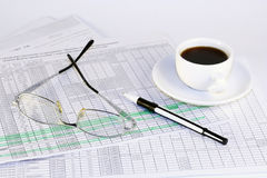 Finances. Glasess, cup of coffee and pen laying on the documents Royalty Free Stock Photos