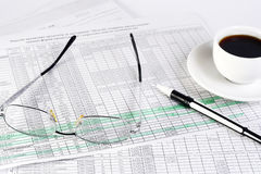 Finances. Glasess, cup of coffee and pen laying on the documents Stock Photos