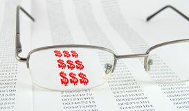 Finances. Page with data and glasses on the top. Through glasses symbol of dollar royalty free stock photo