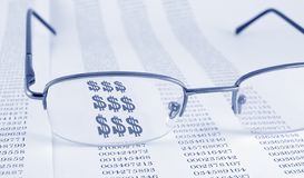 Finances. Page with data and glasses on the top. Through glasses symbol of dollar royalty free stock images