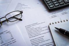 Finances, analyse financière, feuille de calcul de comptabilité de comptes avec des verres de stylo et calculatrice image stock