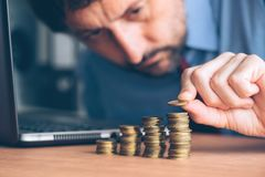 Finances and budgeting, businessman stacking coins. Finances and budgeting, careful businessman stacking coins on office desk stock photo