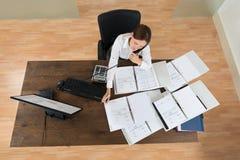 Finances calculatrices d'Attending Call While de femme d'affaires image stock