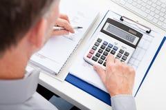 Finances calculatrices d'homme d'affaires Images libres de droits