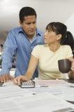 Finances calculatrices de couples à la maison Photographie stock libre de droits