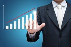 Finances debout de graphique de contact de main de posture d'homme d'affaires dessus au-dessus de fond bleu Photos libres de droits