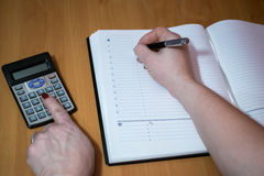 Finances, economy, technology and people concept - close up of woman hands with calculator counting and taking notes to notebook stock photo