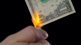 Finances, people, savings and bankruptcy concept - close up of male hand holding burning dollar cash money over black. Finances, savings and bankruptcy concept stock footage