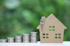 Finances, pile d'argent de pi?ces de monnaie et maison mod?le sur le fond vert naturel, l'investissement productif et les immobil photos stock