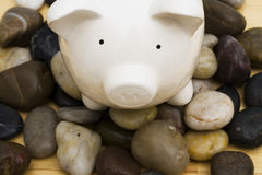 Finances on the Rocks. Piggy bank on rocks,  troubled times in the financial and banking world Royalty Free Stock Images