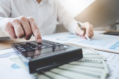 Finances Saving Banking Concept, Man accountant calculations inc. Ome and analyzing financial graph data with calculator stock photography