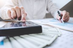 Finances Saving Banking Concept, Man accountant calculations income and analyzing financial graph data with calculator.  royalty free stock photos