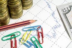 Financez l'anticipation commerciale avec le diagramme, les agrafes de couleur, le crayon et les pièces de monnaie Photographie stock libre de droits