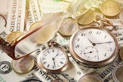 Financez le temps, c'est de l'argent le concept avec de vieilles horloges de vintage, billets d'un dollar, euro pièces et verres Photographie stock libre de droits