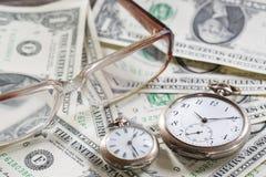 Financez le temps, c'est de l'argent le concept avec de vieilles horloges de vintage, billets d'un dollar, lunettes Photo stock